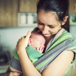 Newborn baby hold by mother in the baby wrap carrier. ** Note: Shallow depth of field