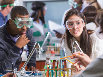 Career Academies: two high school students wearing goggles and listening to a teacher who points a pencil at some chemistry equipment