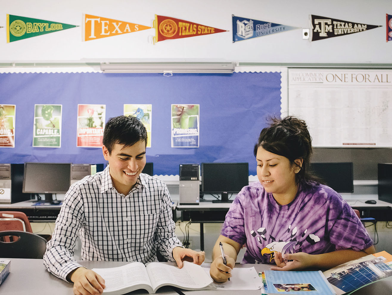 Two young people in a classroom looking at college materials