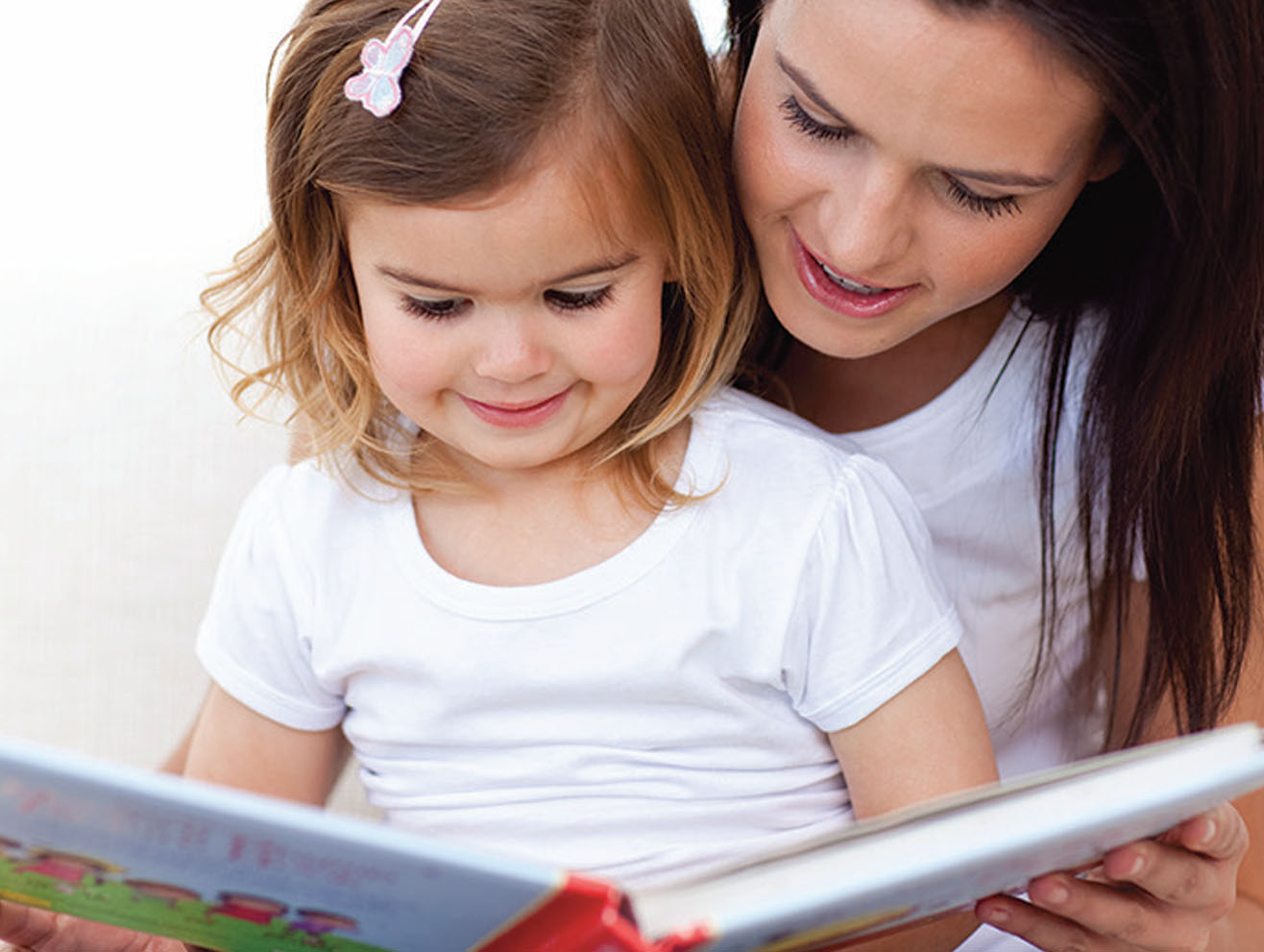 Mother reading a picture book to a preschool girl