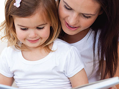 toddler and mother reading together