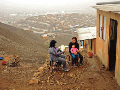 Community health worker sitting with a mother and young child outside a home on a Peruvian hillside,with homes visible in the distance