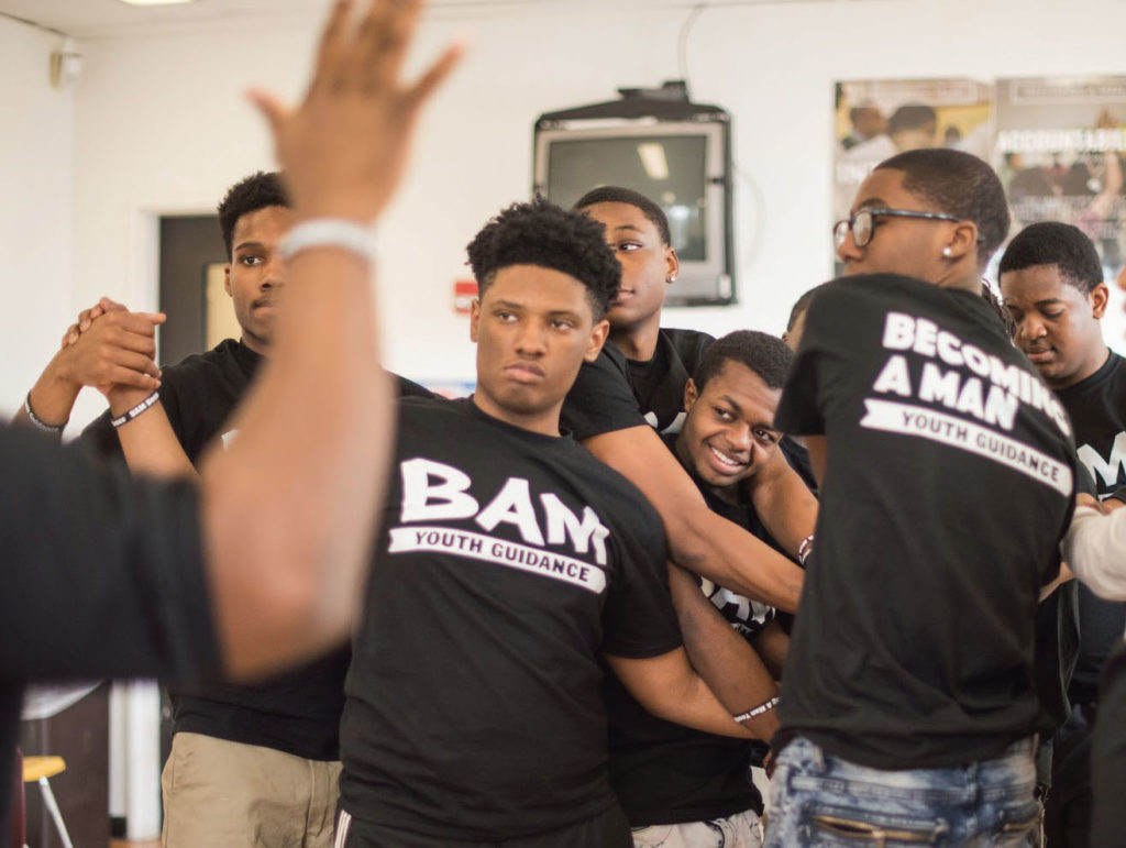 Young men wearing BAM, Becoming a Man, black t-shirts, embracing and clasping hands
