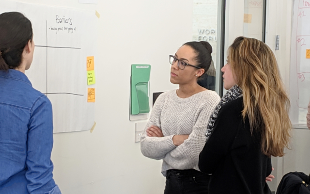 Three female students examining a white board
