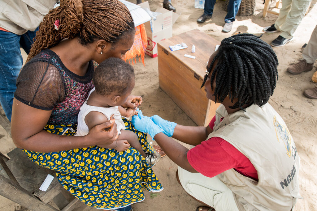 Community health worker delivers care to mother holding baby