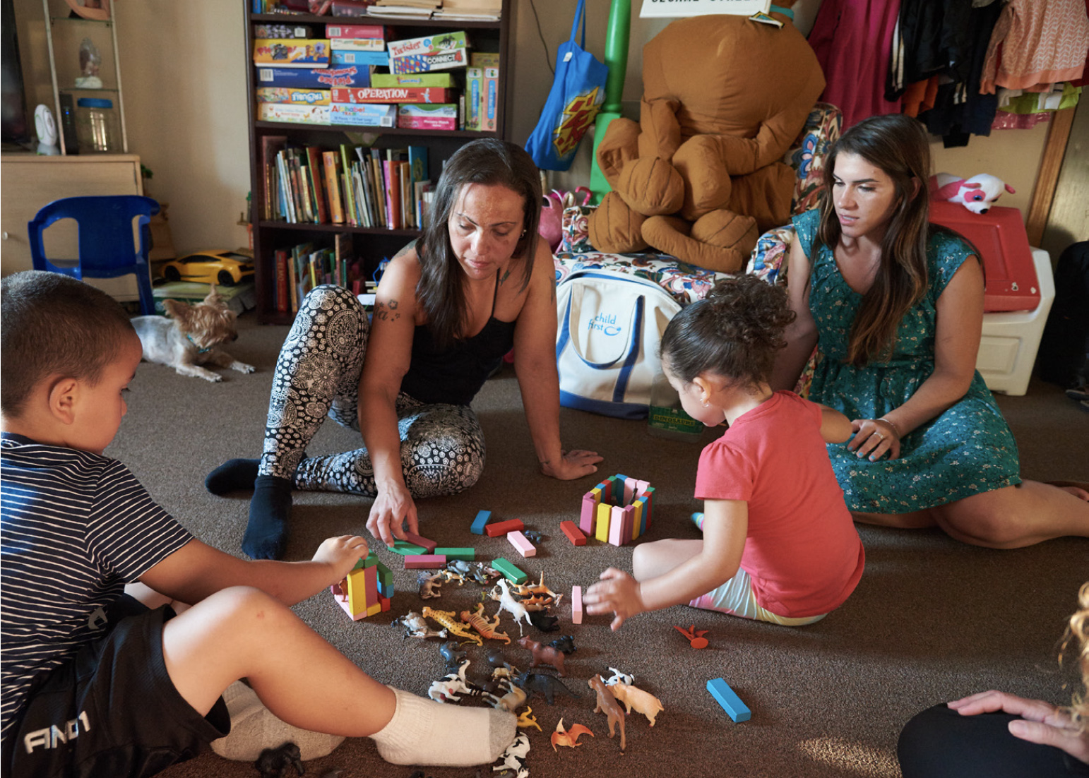 Two women playing on the floor with two children