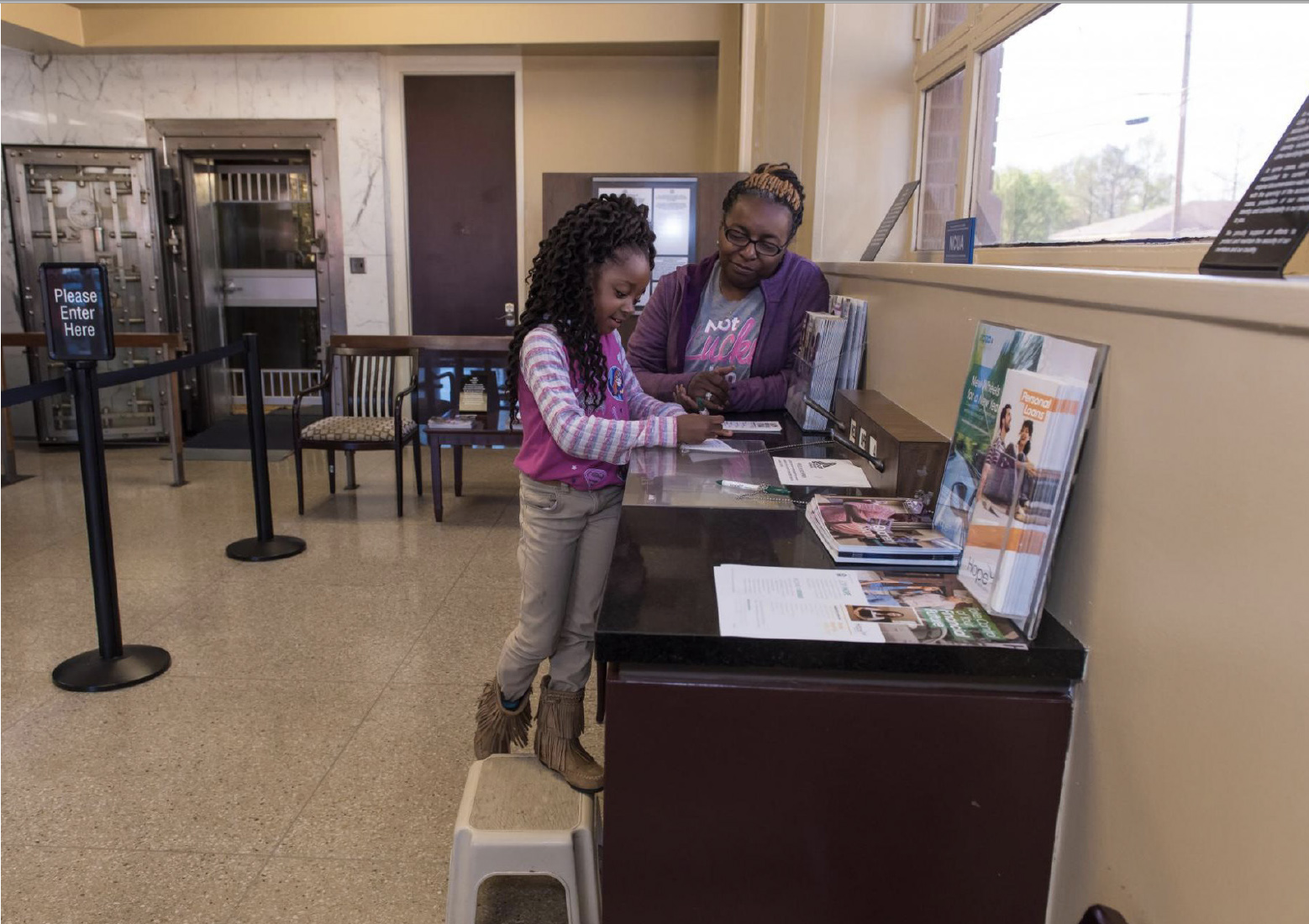Woman helping a child fill out a bank slip