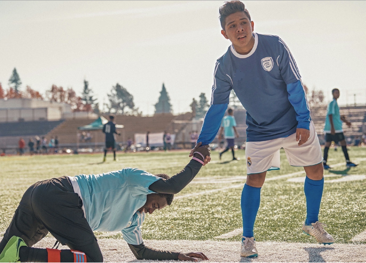 boy in soccer gear helping another boy stand up from where he's fallen on the soccer field