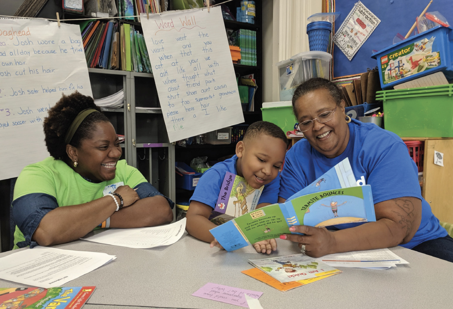 Two smiling woman working to teach a little boy to read